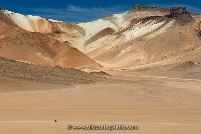 Jeep driving on the Altiplano of Bolivia in front of colorful mountains