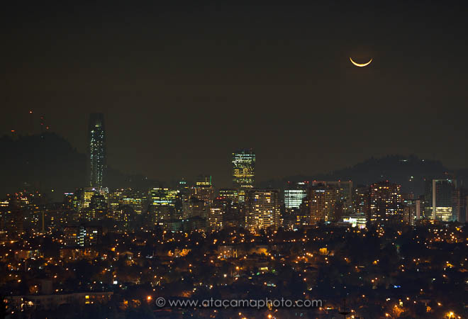 Crescent moon setting over highrisers, night skyline of the city Santiago de Chile