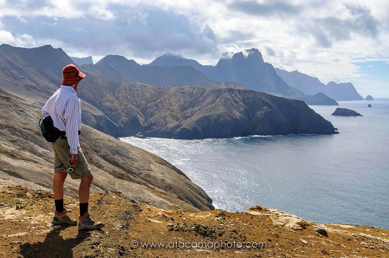 Tourist hiking at the rugged coast of Robinson Crusoe Island