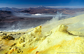 Sulfur fumaroles at the top of volcano Lastarria, with Llullaillaco in the background