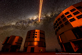 The Paranal telescope domes are reflecting the glow of the laser guide star, which is pointing at the center of the milky way