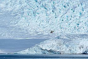 Helicopter flying in front of Murray Glacier at Robertson Bay, Antarctica