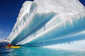 Kayaking between giant icebergs in Antarctica
