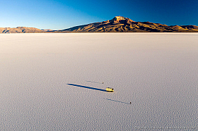 Aerial view of the Uyuni salt flat with Tunupa volcano, a camper and two persons are giving a perspective of the size