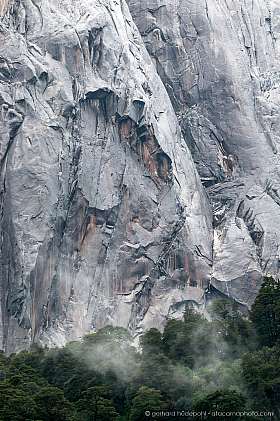 Vertical granite rock wall of Cerro Trinidad, Cochamo Valley in Patagonia Chile. Fog is rising up from the forest at the base