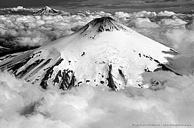 Aerial photo of Snow covered volcano Villarrica above a cloud layer, Lanin in the background