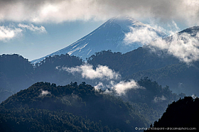 Dramatic clouds and forest silhouette with Lanin volcano in the background. Chile Lake District Los Rios Region