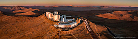 Aerial panorama of Paranal with the VLT and VLTI and the shadow of Paranal next to Cerro Armazones on the horizon. The basecamp to the right.
