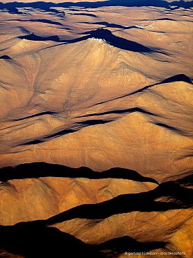 Aerial photo of Paranal Observatory, rolling Atacama desert hills in red evening light