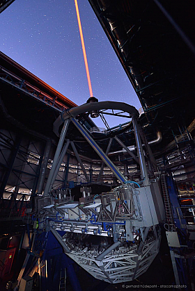 Paranal observatory VLT telescope at twilight with laser in operation