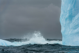 Vertical iceberg face with wave and dark clouds, South Georgia Island